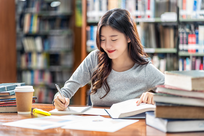 Asian young Student in casual suit reading and doing homework in library of university or colleage with various book and stationary on the wooden table over the book shelf background, Back to school